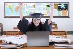 Opgewekte leerling met graduatietoga in klasse Stock Foto