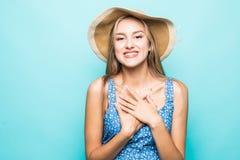 Opgewekte leuke jonge vrouw in strohoed status geïsoleerd over blauwe achtergrond stock afbeeldingen