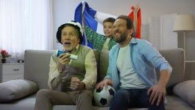 Opgewekte mannelijke familieleden die voor Frans het kampioenschapshuis van het voetbalteam toejuichen stock video