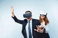 Opgewekte medewerkers die pret hebben terwijl samen het spelen van virtuele spelen Stock Foto's