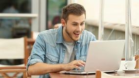 Opgewekte mens die goed nieuws in laptop lezen stock video
