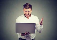 Opgewekte mens die groot nieuws op zijn laptop lezen royalty-vrije stock foto's