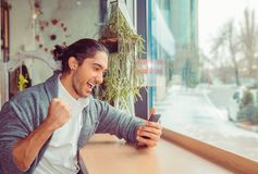 Opgewekte mens die nieuws controleren op smartphone stock afbeeldingen