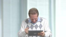 Opgewekte mens die PC-tablet op vage achtergrond gebruiken stock videobeelden