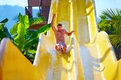 Opgewekte mens die pret op waterdia hebben in tropisch aquapark Royalty-vrije Stock Foto's