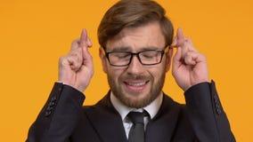 Opgewekte mens die vingers, zenuwachtig over wens kruisen, die wens, close-up maken stock footage
