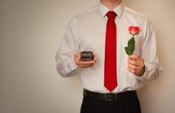 Opgewekte mens in overhemd en rode band, die een trouwringdoos houden Royalty-vrije Stock Foto