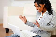 Opgewekte modieuze vrouw die aan laptop het scherm kijkt Stock Afbeelding