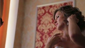 Opgewekte mooie blondebruid in het schitterende modieuze witte huwelijkstoga stellen bij kleedkamer vóór de ceremonie stock footage