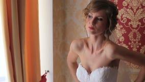 Opgewekte mooie blondebruid in het schitterende witte toga stellen bij kleedkamer vóór huwelijk stock video
