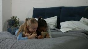 Opgewekte multi etnische jonge geitjes die op video op telefoon letten stock video