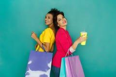 Opgewekte multi-etnische meisjes met het winkelen zakken en koffiekop Stock Fotografie