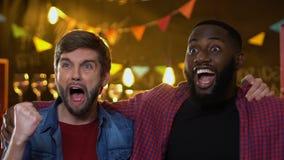 Opgewekte multiraciale mannelijke vrienden die het favoriete doel van het sportenteam verheugen zich in bar stock footage