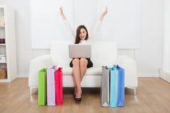 Opgewekte onderneemster die met laptop online op bank winkelen Stock Foto's