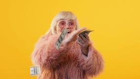 Opgewekte oude dame die dollarrekeningen werpen rond, de financiële investering van de loterijwinst stock footage