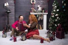 Opgewekte rijpe vrouw die met Kerstmis huidig van haar echtgenoot worden tevredengesteld royalty-vrije stock fotografie
