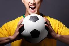 Opgewekte sportmens die en voetbal houden schreeuwen Royalty-vrije Stock Foto's