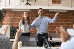 Opgewekte teamleider die werknemer met bevordering gelukwensen terwijl royalty-vrije stock afbeelding