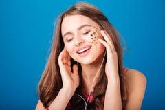 Opgewekte tedere jonge vrouw die aan muziek en het zingen luisteren Stock Afbeelding