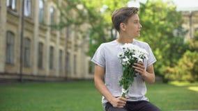 Opgewekte tienerjongen die met boeket van bloemen op meisje, anticiperen wachten stock video