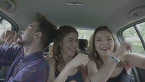 Opgewekte tienervrienden die en auto van rit genieten die samen lachen dansen - stock videobeelden