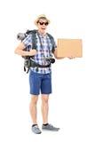Opgewekte toerist die een leeg kartonteken houden Royalty-vrije Stock Foto