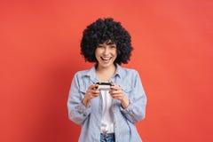 Opgewekte toevallige jonge vrouw het spelen videospelletjes die pret op rode achtergrond hebben royalty-vrije stock foto's