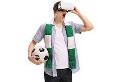 Opgewekte voetbalventilator die een VR-hoofdtelefoon met behulp van Stock Foto's