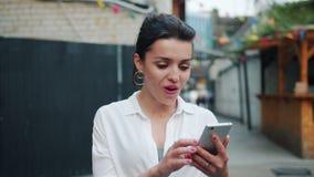 Opgewekte volwassen vrouw die smartphone in openlucht na het krijgen van groot nieuws bekijken stock videobeelden