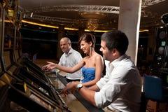 Opgewekte vrienden die bij gokkenmachines spelen Royalty-vrije Stock Afbeeldingen