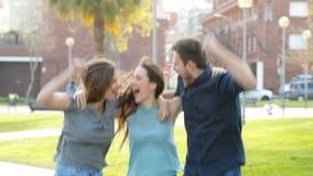 Opgewekte vrienden die het vieren succes springen stock videobeelden