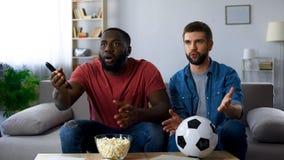 Opgewekte vrienden die op voetbalwedstrijd letten die, door nederlaag van favoriet team wordt gefrustreerd royalty-vrije stock foto's