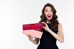 Opgewekte vrolijke aantrekkelijke jonge vrouw met retro kapsel het openen gift Stock Fotografie