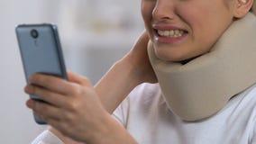 Opgewekte vrouw in cervicale smartphone van de kraagholding, pijn van de gevoels de scherpe hals stock video