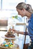 Opgewekte vrouw die doughnuts van caketribune selecteren Royalty-vrije Stock Foto