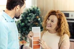 Opgewekte vrouw die kaarten met kleuren tonen aan haar echtgenoot Stock Foto