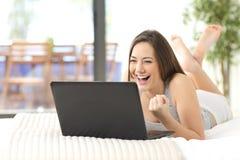 Opgewekte vrouw die online het letten op laptop winnen Stock Afbeeldingen