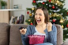 Opgewekte vrouw die op TV op Kerstmis letten royalty-vrije stock foto