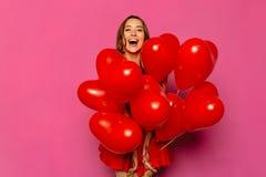 Opgewekte vrouw die rode ballons houden Royalty-vrije Stock Fotografie