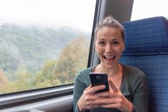 Opgewekte vrouw een smartphone en winnen houden die op de treinreis online stock afbeeldingen