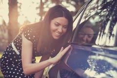 Opgewekte vrouw en haar nieuwe auto met zonovergoten bos op achtergrond royalty-vrije stock foto