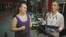 Opgewekte vrouw opleiding in gymnastiek, die aan voedingsdeskundige spreken, door resultaten wordt gemotiveerd stock video