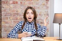 Opgewekte vrouwelijke studentenzitting bij de lijst met smartphone Stock Fotografie