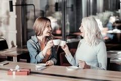 Opgewekte vrouwen van verschillende leeftijd zitting en het drinken koffie samen stock fotografie