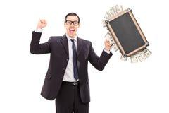 Opgewekte zakenman die een zakhoogtepunt van geld houden Stock Afbeeldingen