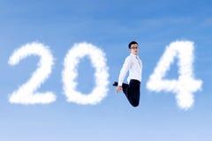 Opgewekte zakenman die met wolken van 2014 springen Royalty-vrije Stock Afbeelding