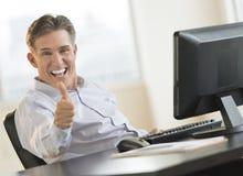 Opgewekte Zakenman Gesturing Thumbs Up bij Bureau Stock Afbeeldingen