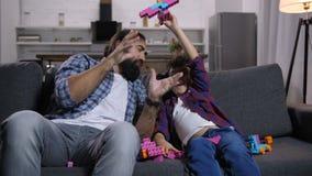Opgewekte zoon en papa die van tijdverdrijf met speelgoed genieten stock video