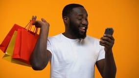 Opgewekte zwarte mannelijke holding het winkelen zak en smartphone, de contant geld achterdiensten stock videobeelden