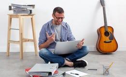Opgewonden creatieve ondernemerszitting op vloer om te ontspannen en te werken Stock Afbeeldingen